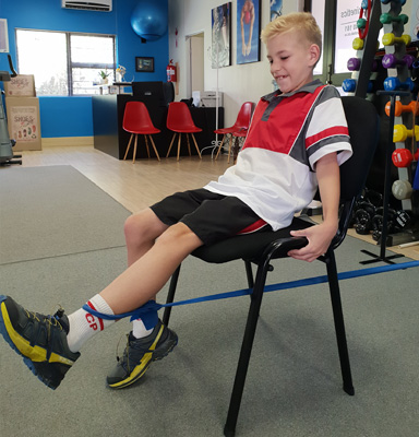 Young boy doing leg extensions